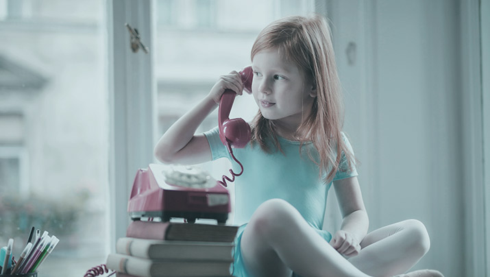 A child speaking with an old style telephone to her ear