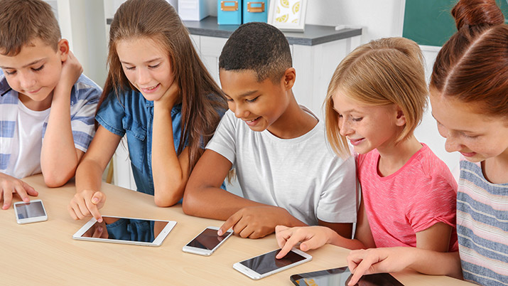 A mixed group of children looking at smart devices